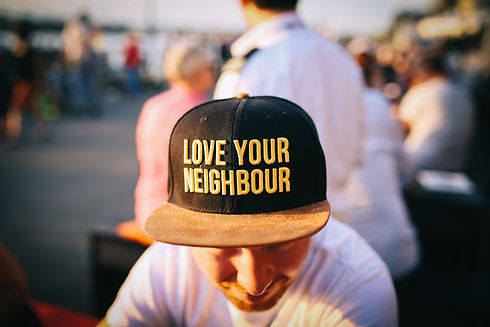 """Image of a young man wearing a yellow and black cap that reads """"LOVE YOUR NEIGHBOUR"""""""