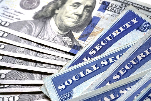 Image of Social Secutiy cards and one-hundred dollar bills next to each other.