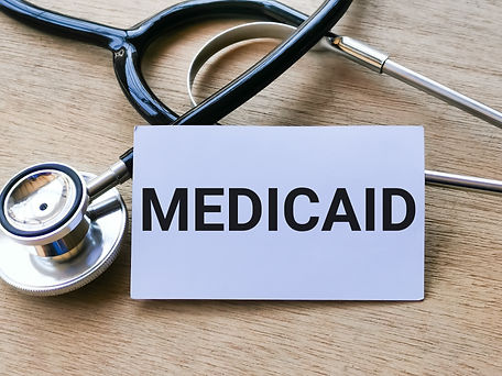 """Image of a white card with the phrase """"MEDICAID"""" written on it, placed in front of a stethoscope."""