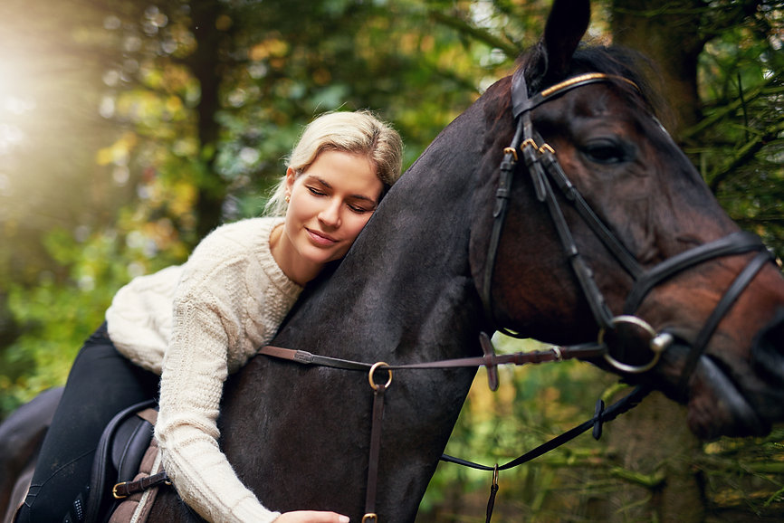 smiling-woman-hugging-her-horse-in-park-