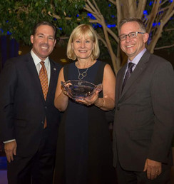 Executive Director of MHNHS accepting an award from Executive Director of MetroHousing Chris Norris and CEO of Eastern Bank Robert Rivers