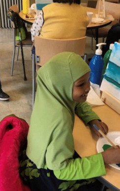 A young resident enjoying an art class in the community room