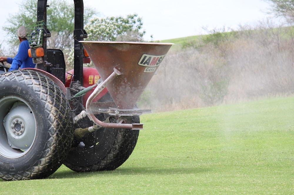 Maquinaria fertilizando el campo de golf y fairways