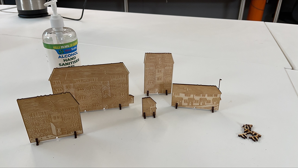5 Laser Cut buildings (Plywood), with a small pile of crosshairs next to the buildings. In the background is hand sanitiser