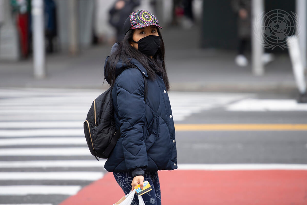 A woman is wearing a mask as she walks to her destination during the Coronavirus (COVID-19) outbreak in New York City. UN7859210 UN Photo