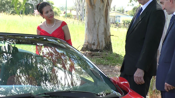 Australian actress in red dress next to red car