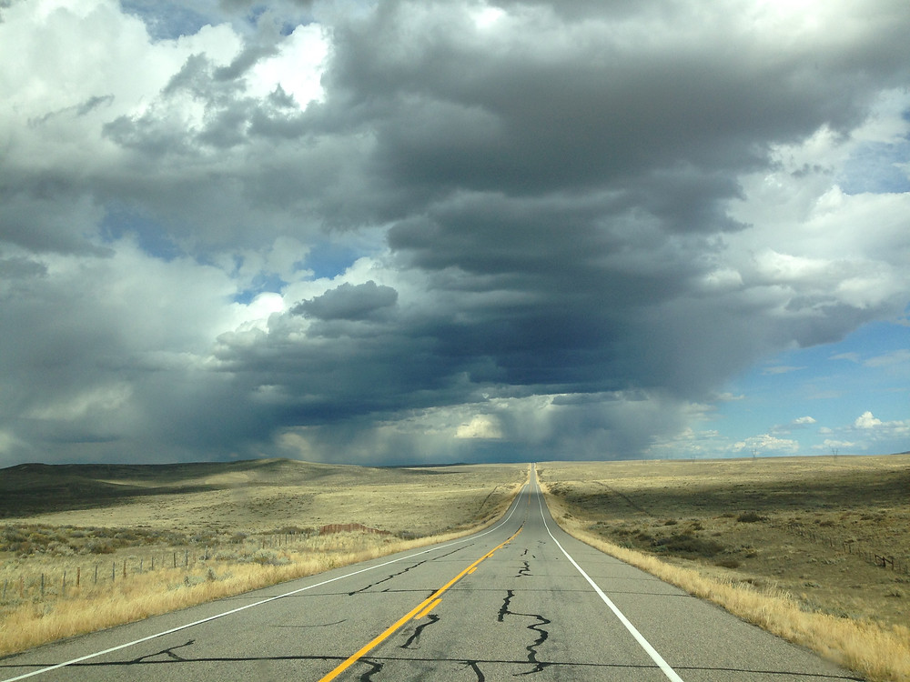 lonely Colorado highway with hovering clouds