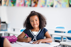 a-small-school-girl-sitting-at-the-desk-