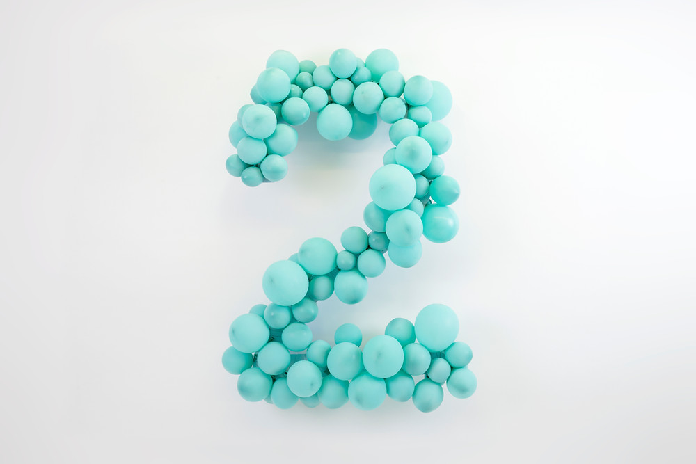 A cluster of turquoise party balloons arranged to shape a number 2 on a white background.