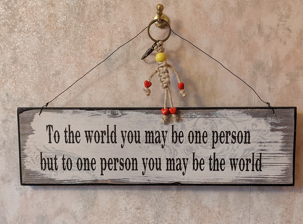 "A hanging sign with words that read: ""To the world you may be one person, but to one person you may be the world""."