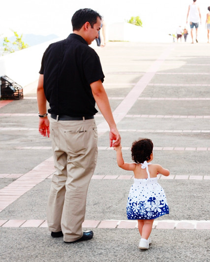 Father and very young daughter walking hand in hand