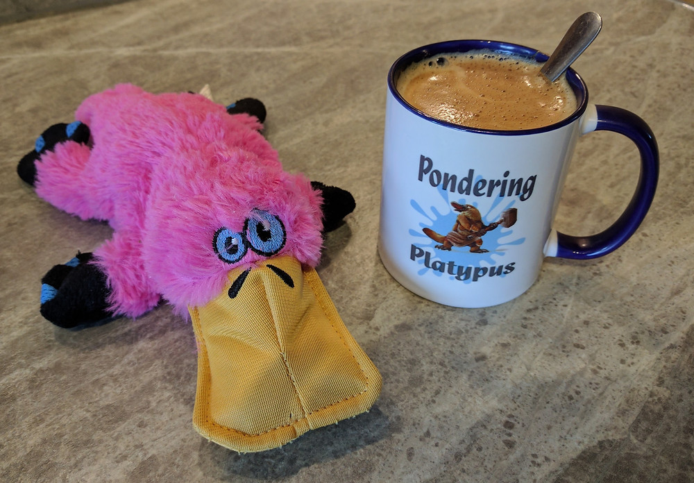 A pink platypuss next to a cup of hot milky coffee. The mug has a platypus wielding a mallet and the words Pondering Platypus on it.