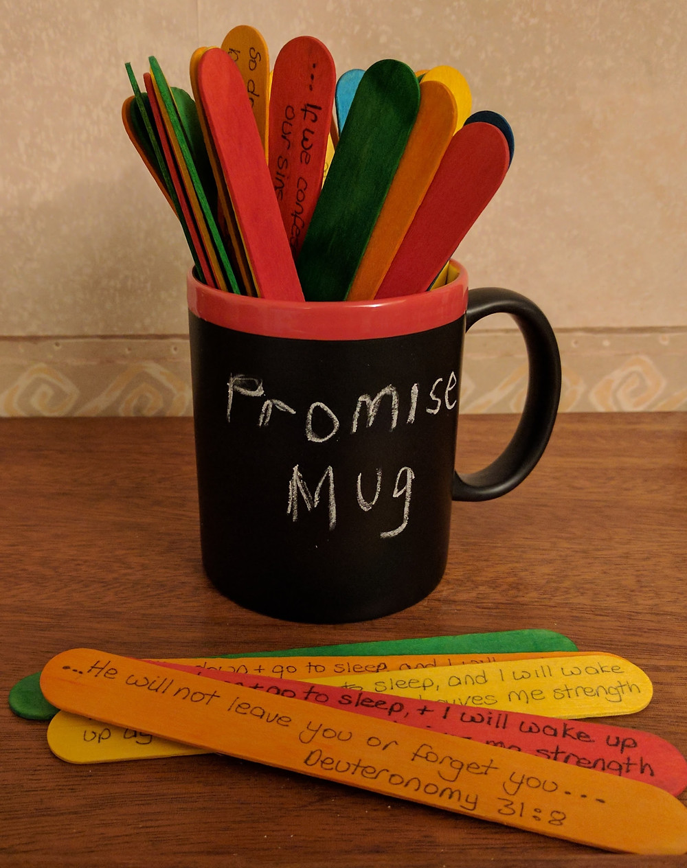 "A mug painted with blackboard paint, with ""Promise Mug"" written in chalk on the side. THe mug is filled with wide coloured lollipop sticks with Bible promises written on them."