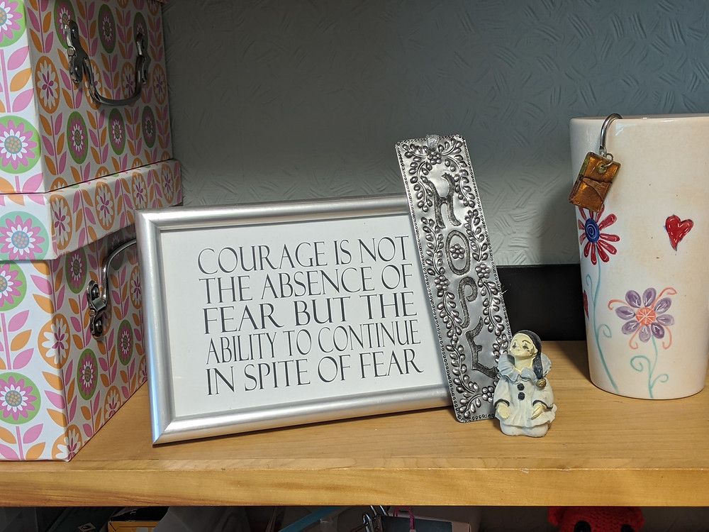 "Postcard that says ""Courage is not the absence of fear, but the ability to continue inspite of the fear. Next to it is a tin bookmark that has the word HOPE on it, and next to that a small pottery figure in a prayerful pose."