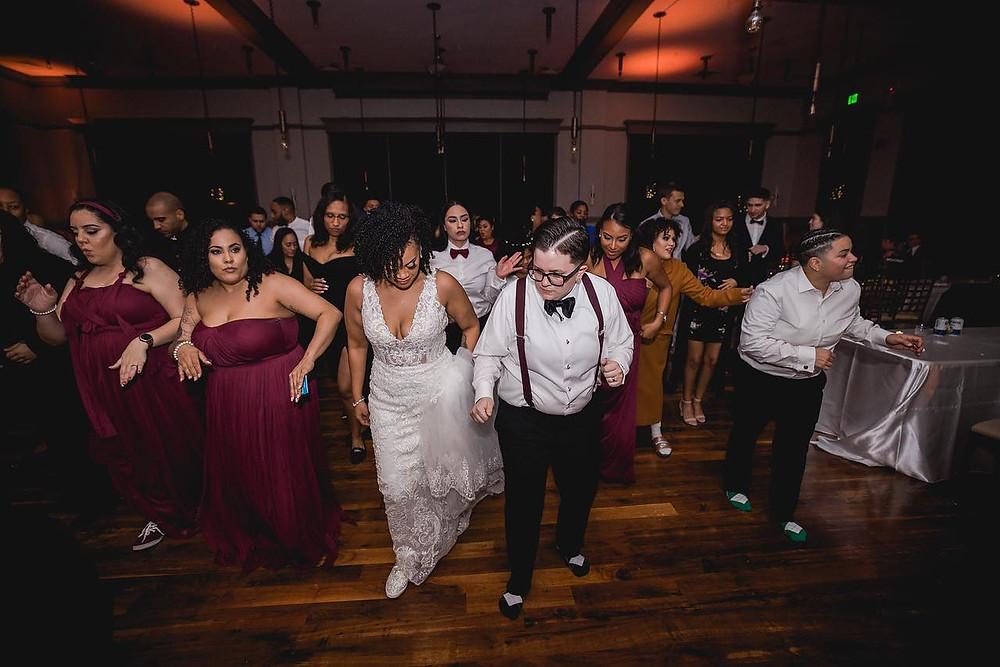 wedding guests line dancing with wedding couple