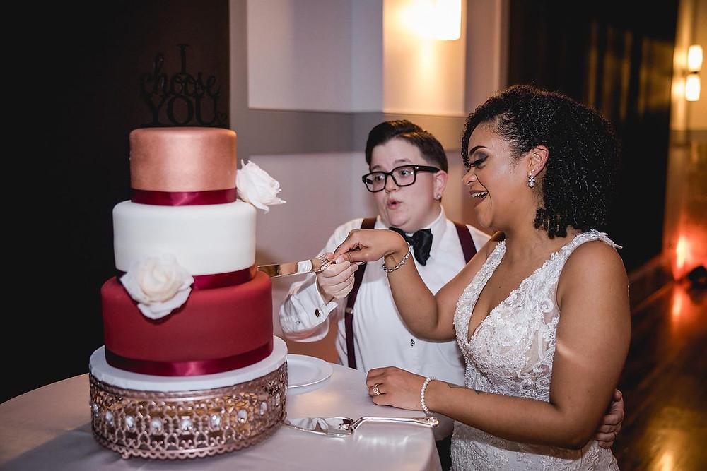 wedding couple cutting into wedding cake