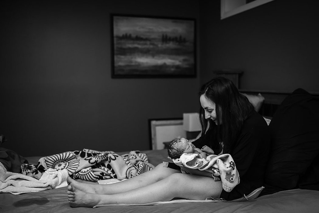 Mother smiling at her newborn after homebirth