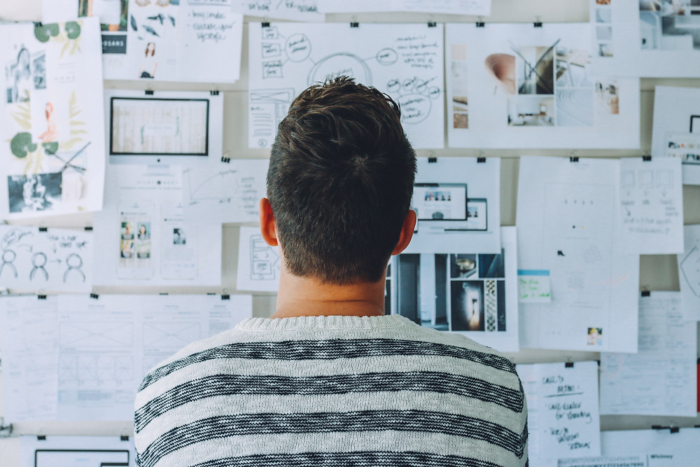 man looking at wall of design plans