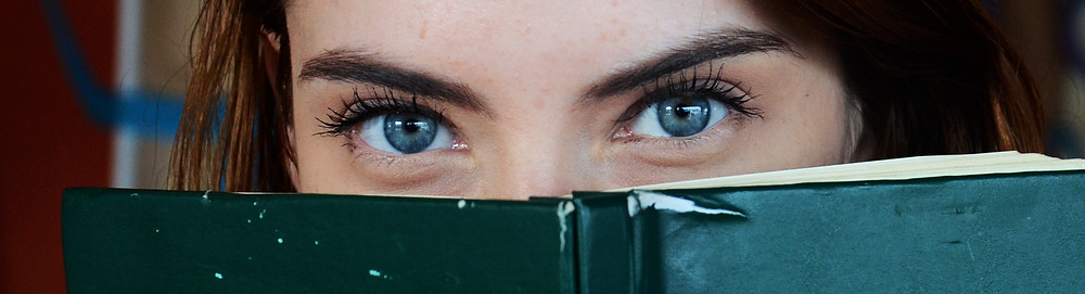 Women's eyes looking over the top of a book