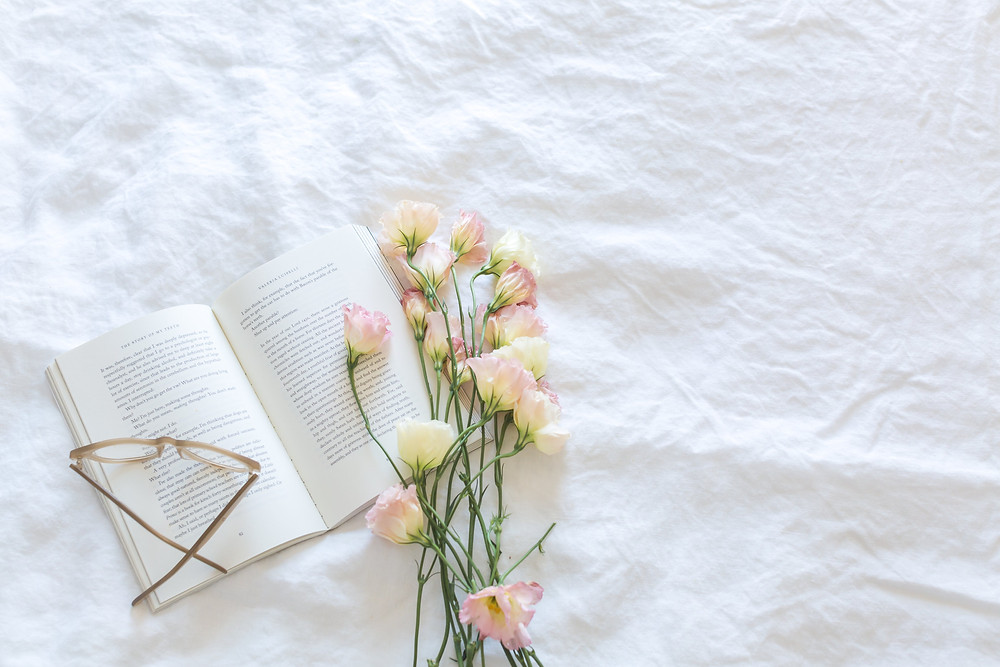 book open on a bed with glasses and flowers