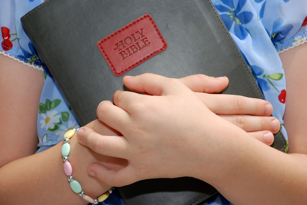 young girl holding the Holy Bible