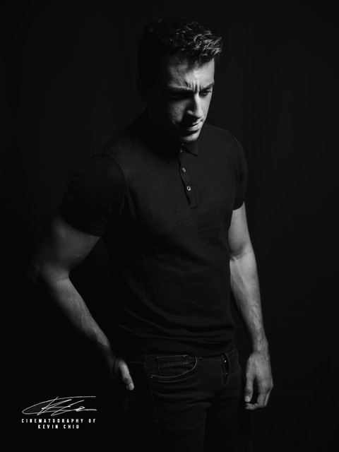 Black and white portrait of man in a black shirt against black backdrop