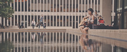 A wide of a woman sitting above an artificial lake at Lincoln Center.