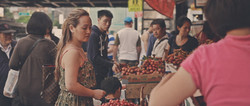 A woman looking at fruit at a supermarket.