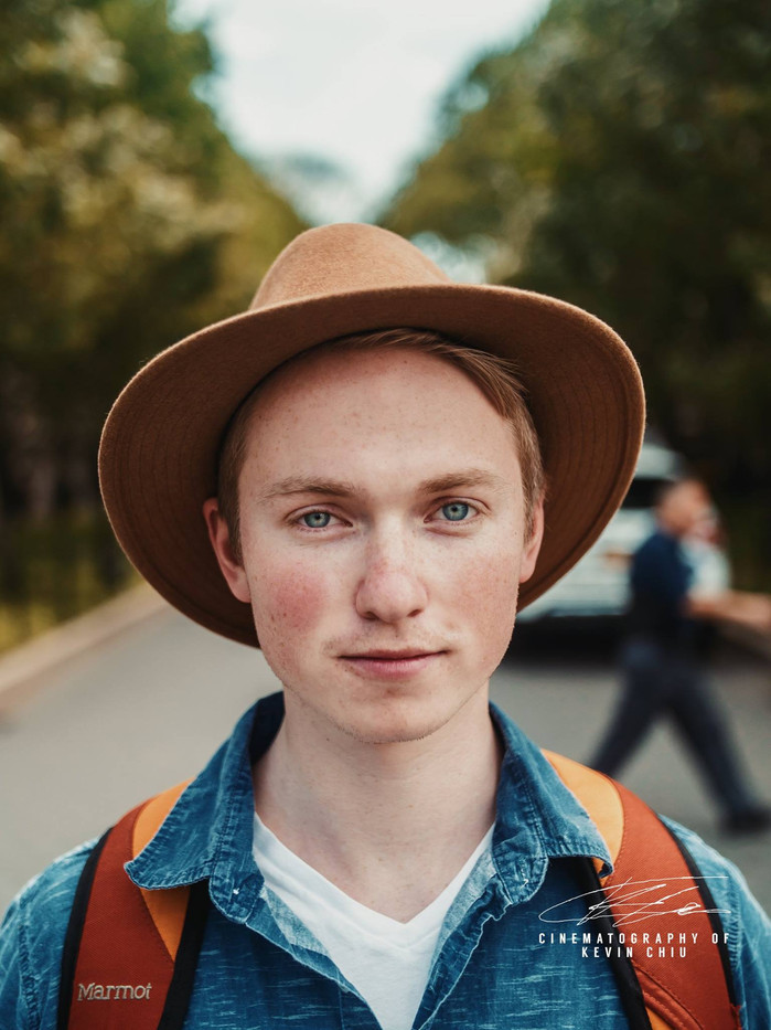 Close up of a man in a hat in front of trees