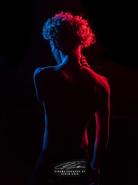 Back of man with red and blue lights against black backdrop