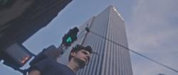 A man underneath a large skyscraper.