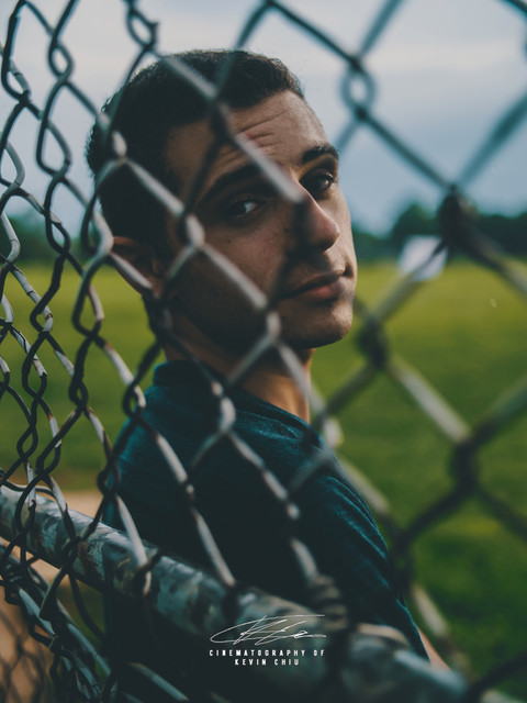 Male model leaning on opposite side of a fence