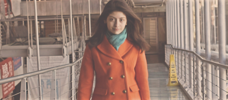 A woman in an orange jacket walking towards camera.
