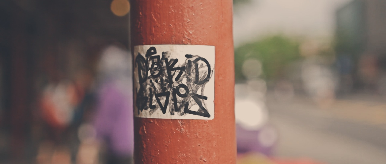 A close up of a graffitied sticker on a pole.
