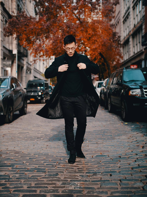 A man with long jacket walking down New York street