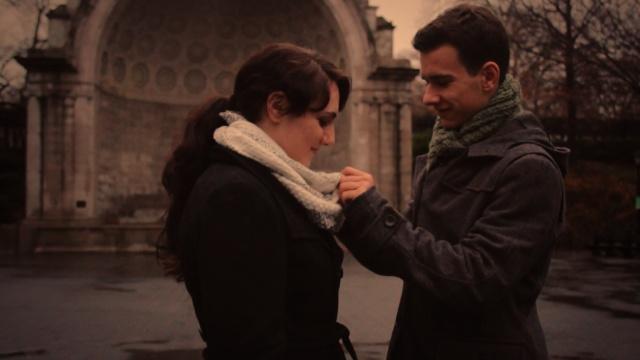 A man adjusting a woman's scarf.
