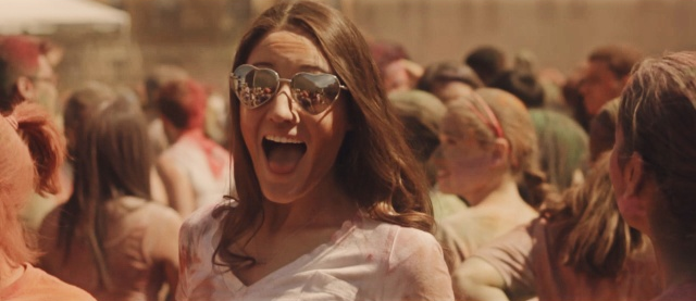 A girl smiling while at a Holi festival.