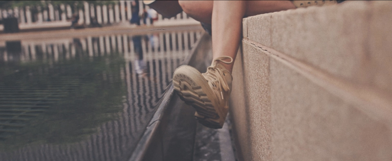 A woman's foot near the water of an artificial lake.