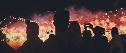 Silhouette of a group of people looking at fireworks.