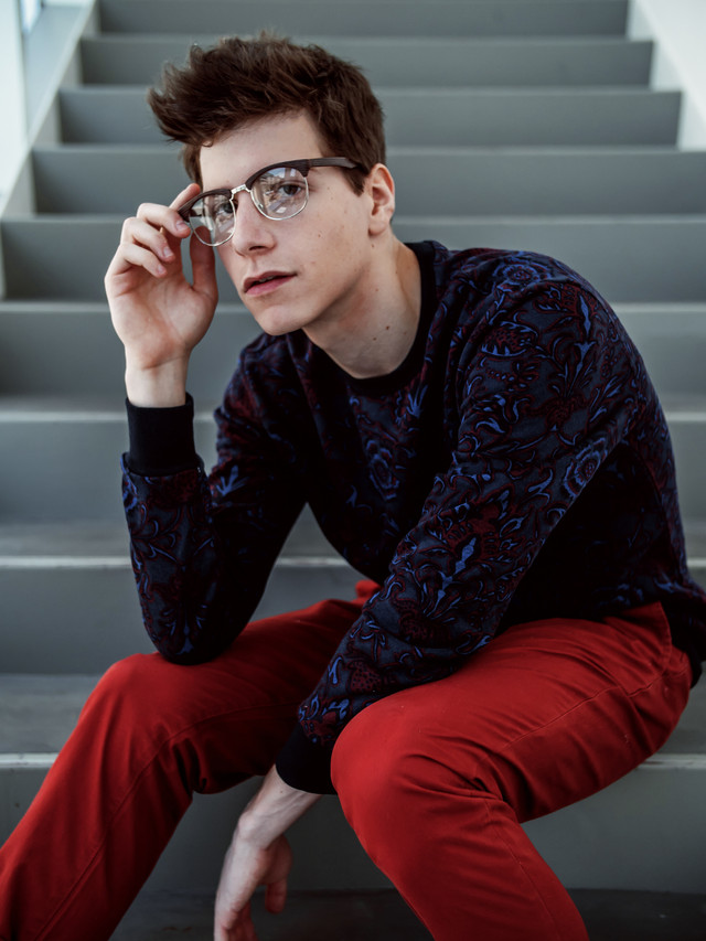 A male model sitting on staircase and holding his glasses