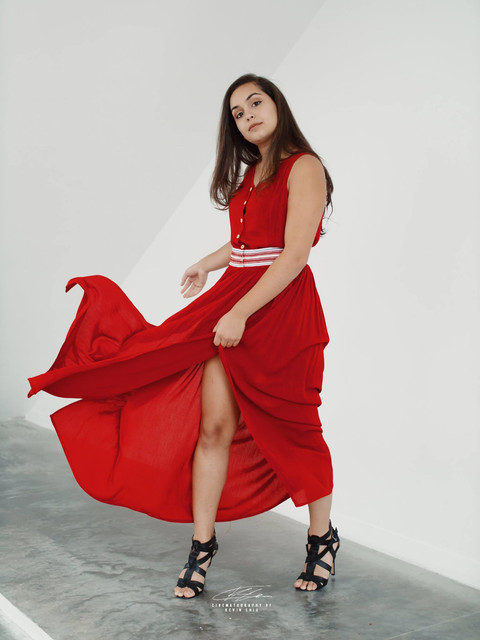 Woman swinging red dress against white backdrop