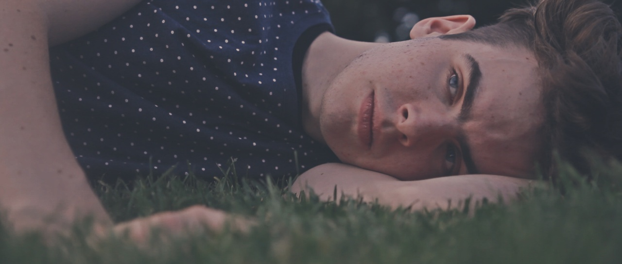 A man lying in the grass looking up