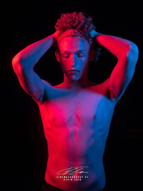 Shirtless male model holding hair lit with red and blue lights
