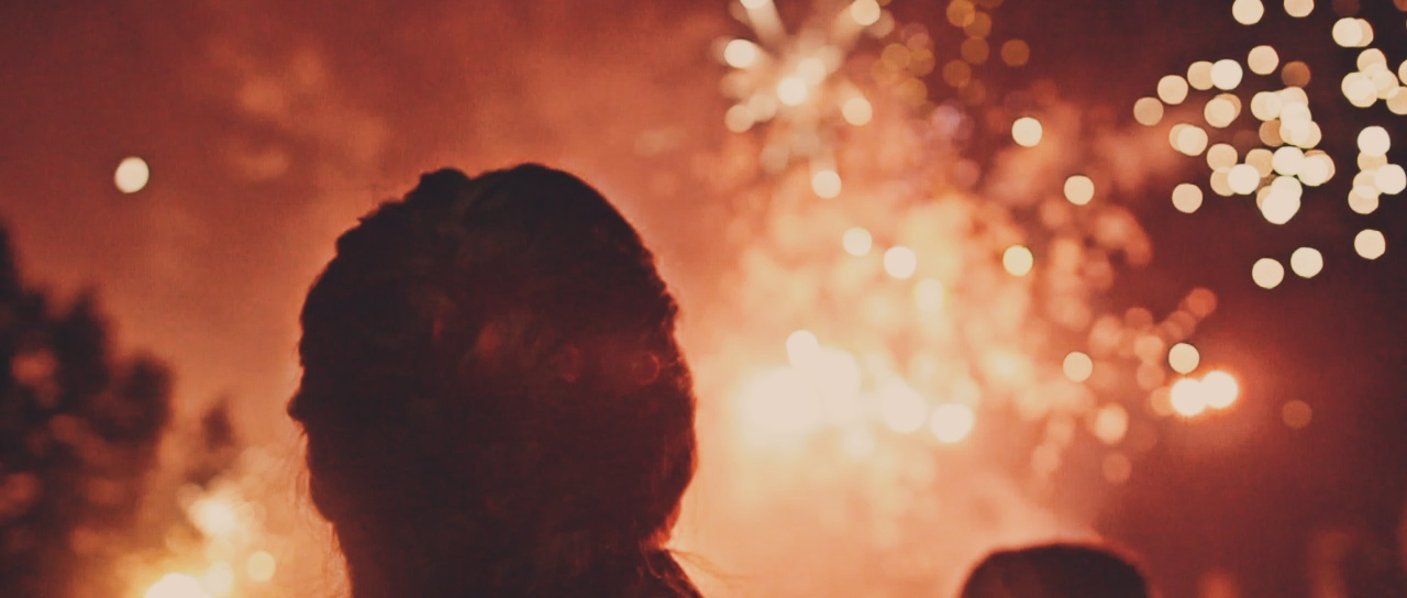 Silhouette of a woman looking at fireworks.