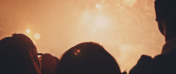 Silhouette of people looking at fireworks.