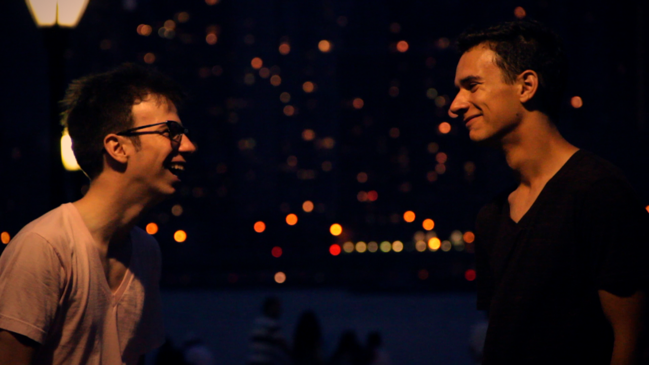 Two teens smiling at each other against a night backdrop of New York City