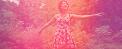 A pink tinted photo of a woman dancing in a park.