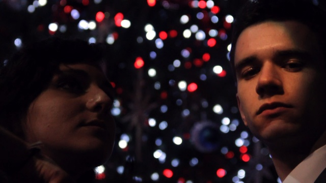 A man and a woman looking at the camera with Christmas tree lights behind them.