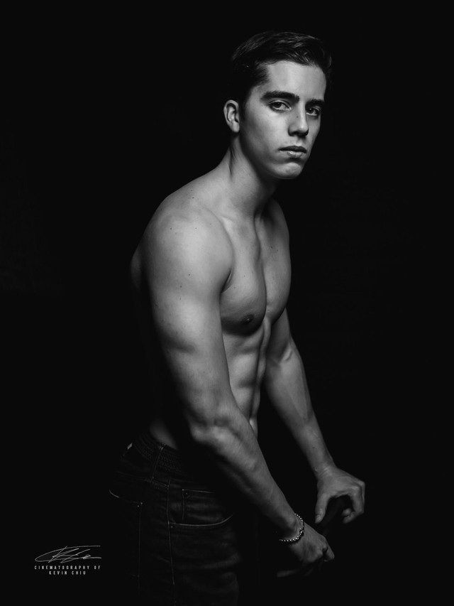 Black and white portrait of shirtless male model against black backdrop