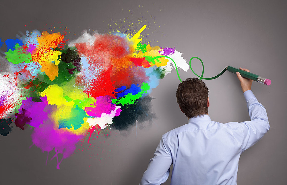 Businessman painting abstract colorful design on gray background